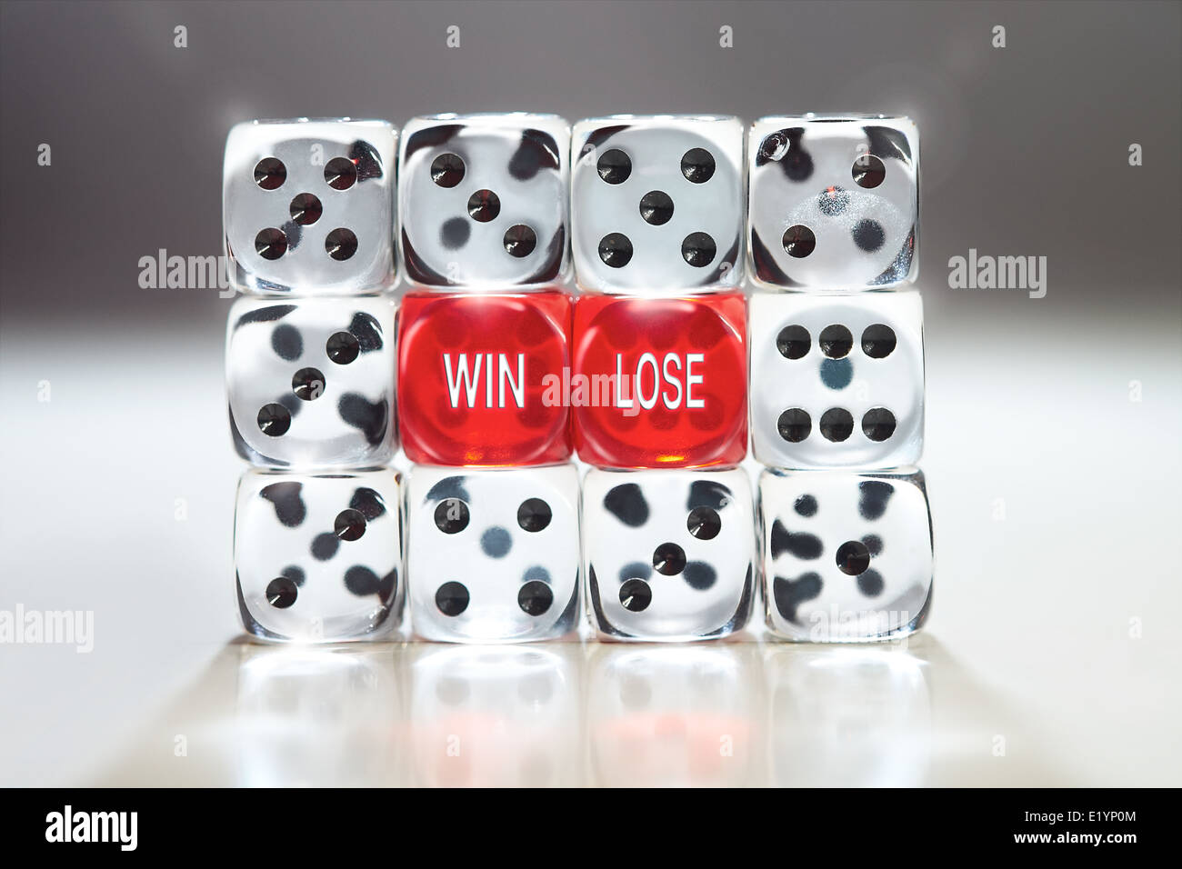 Win lose concept with two red dice supported in a wall of clear dice. - Stock Image