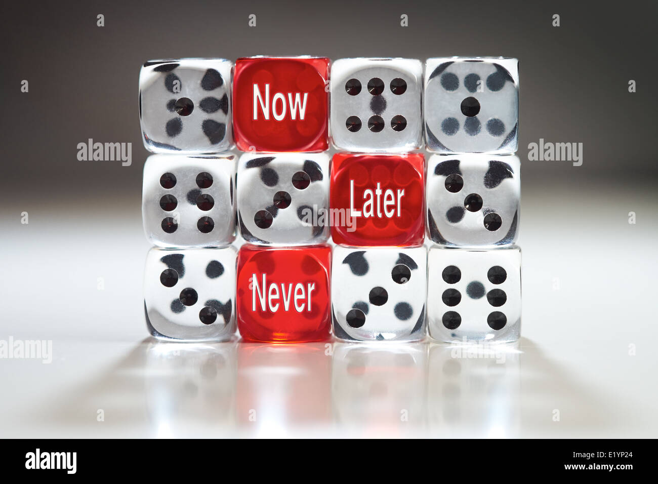 Wasting time concept, three red dice with Now, Later and Never in a wall of clear dice. - Stock Image