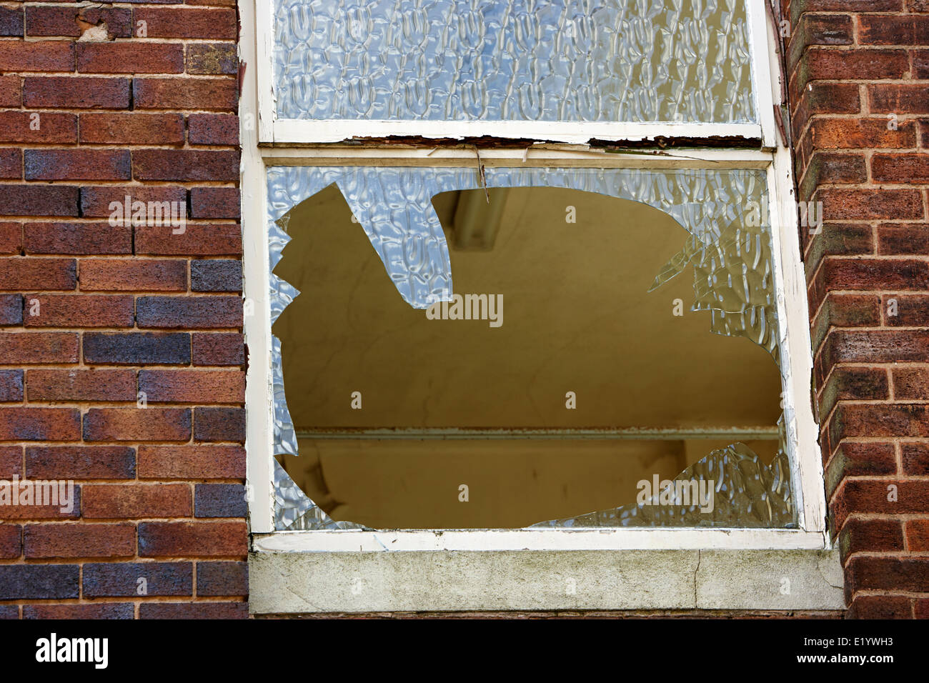 smashed broken window in an abandoned sixties office building England UK - Stock Image