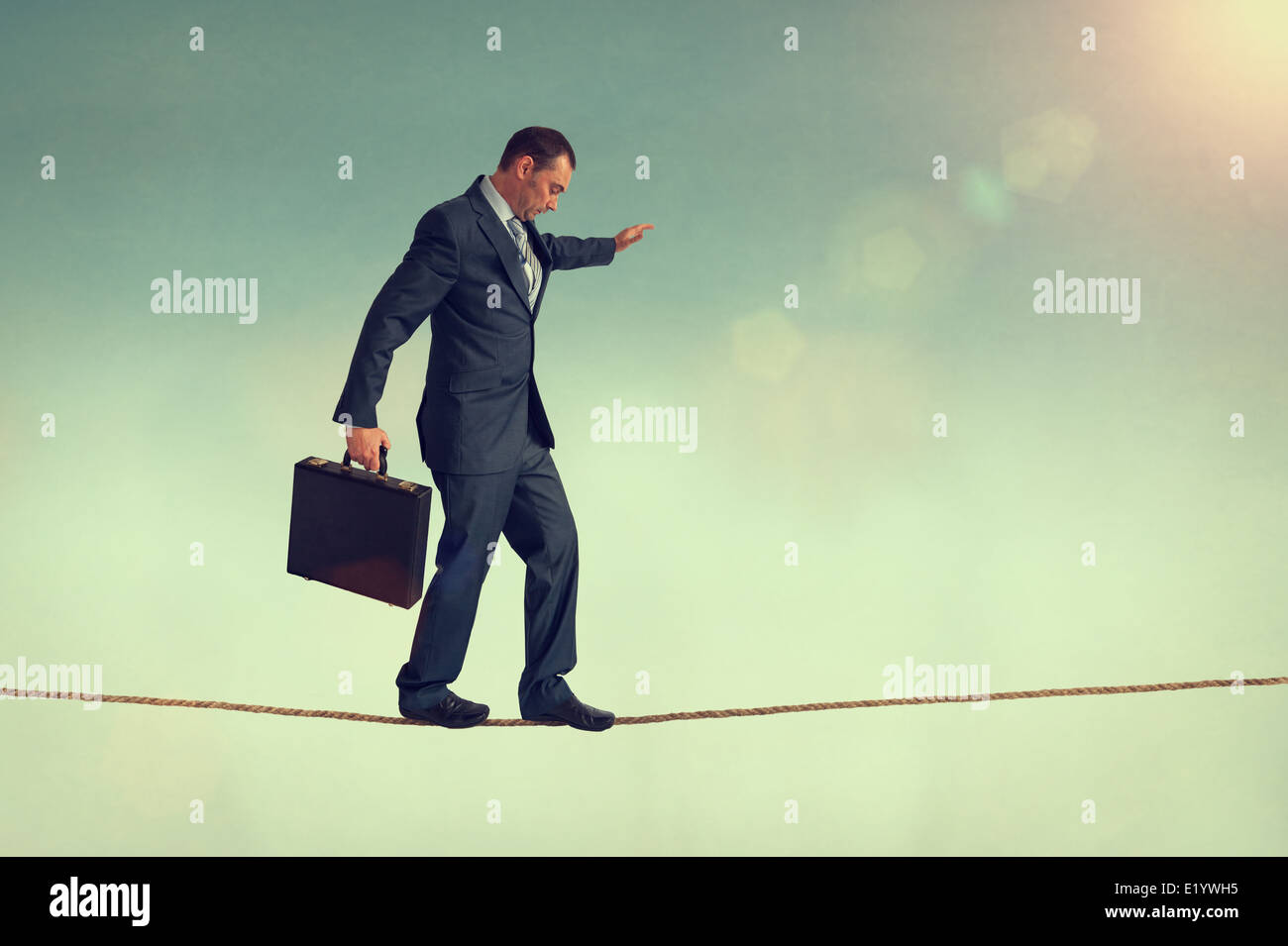 courageous businessman balancing on a tightrope or highwire - Stock Image