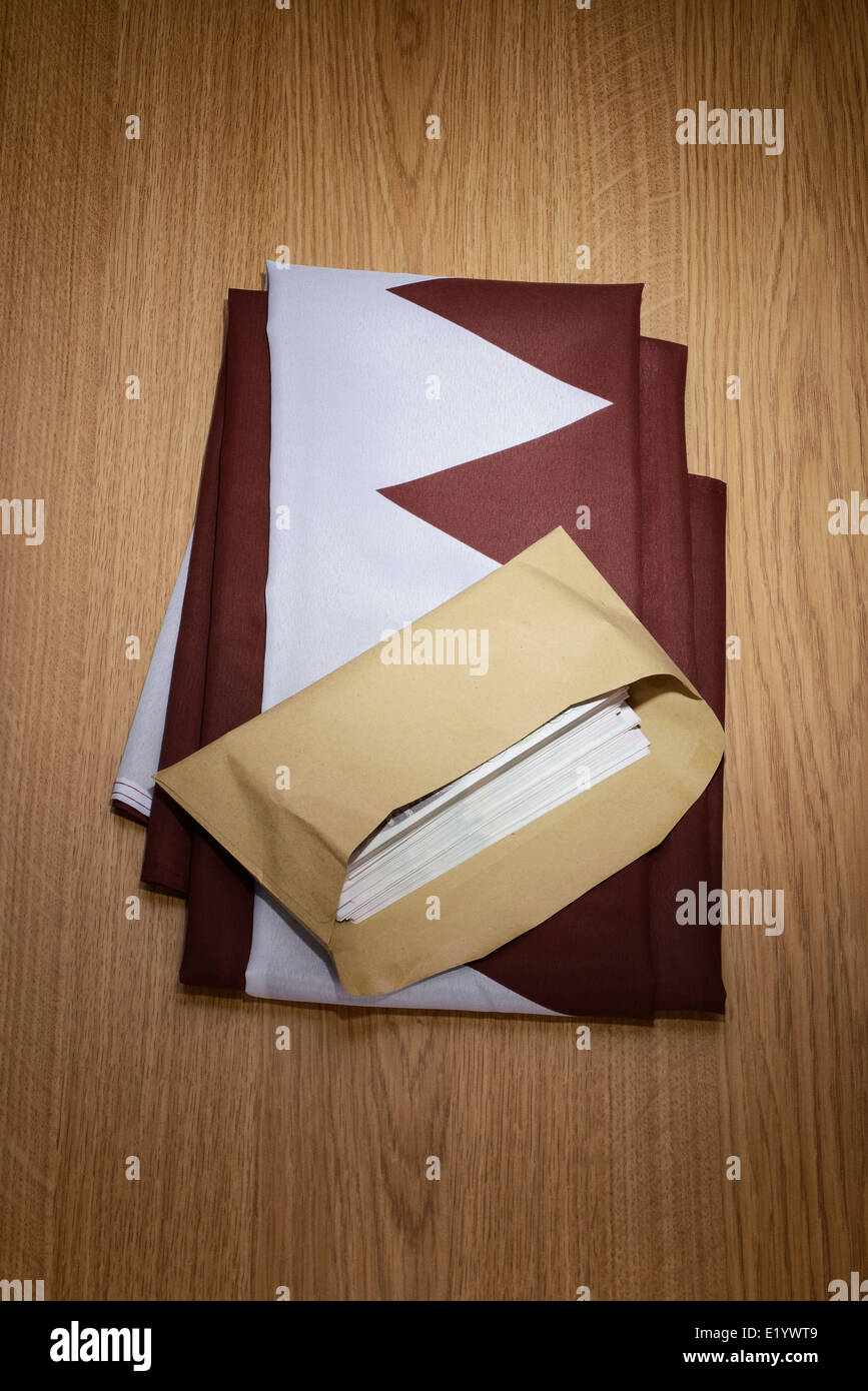 Qatar flag with a brown envelope full of money Stock Photo