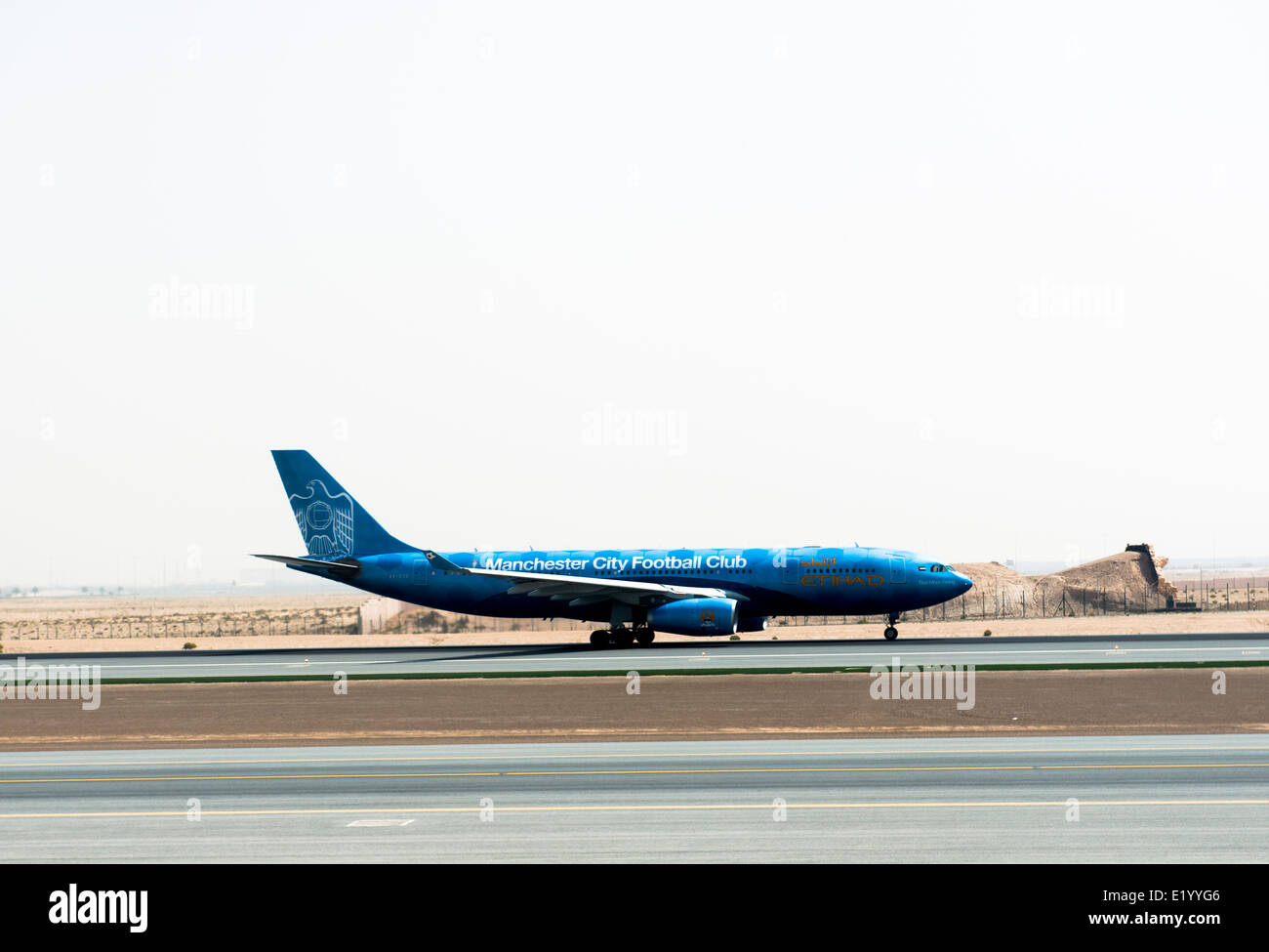 An Etihad airways airplane on the runway at the airport in Abu Dhabi. - Stock Image