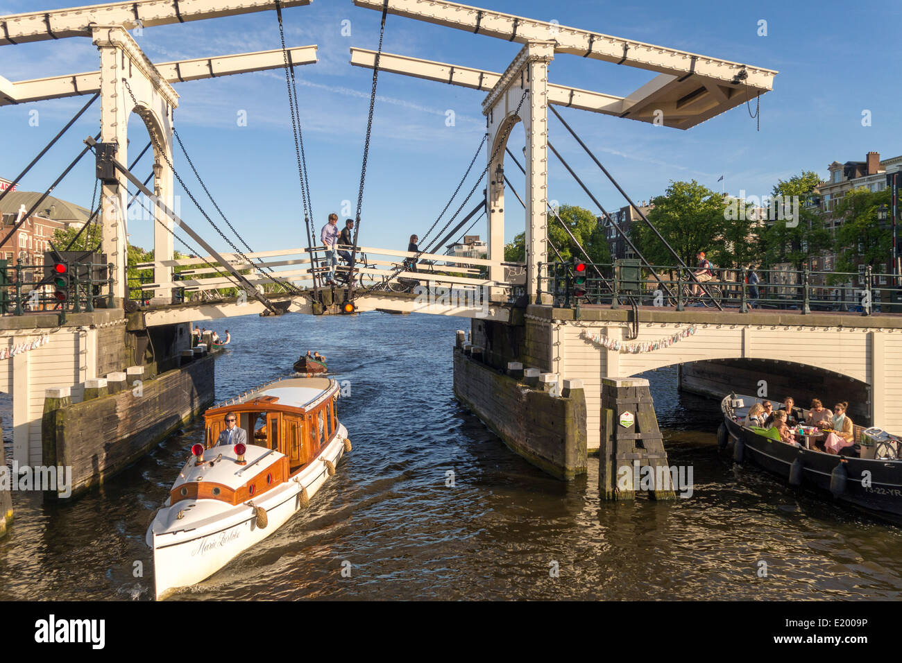 Amsterdam small vintage private VIP canal cruise boat with Magere Brug, Skinny Bridge on the Amstel River - Stock Image