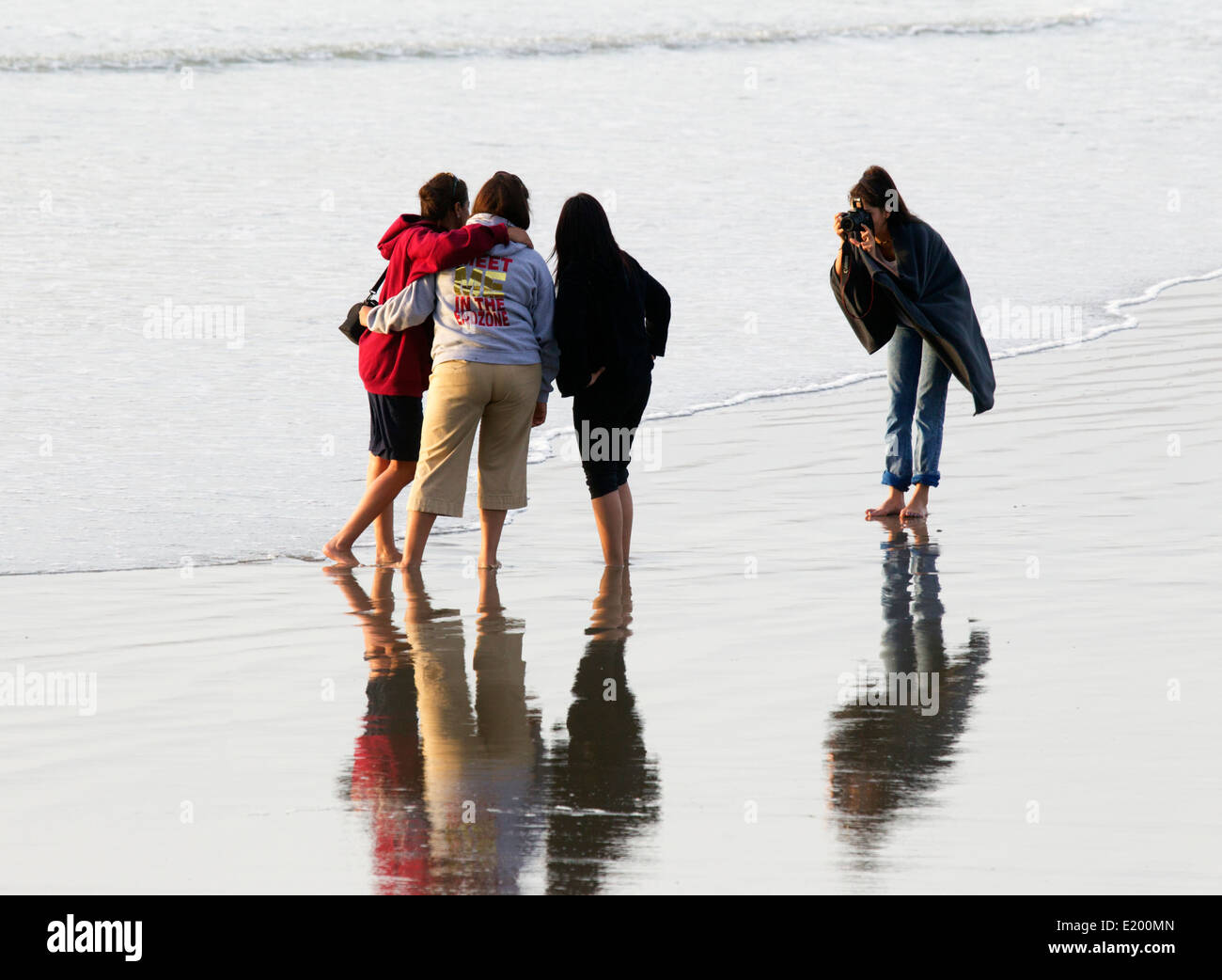 Three Girls at the Seashore Being Photographed by a Fourth Girl - Stock Image
