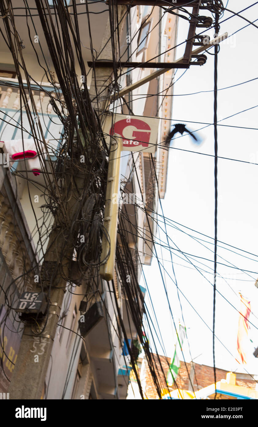 Kathmandu Nepal where a pigeon flies through a mess of power line-wires - Stock Image