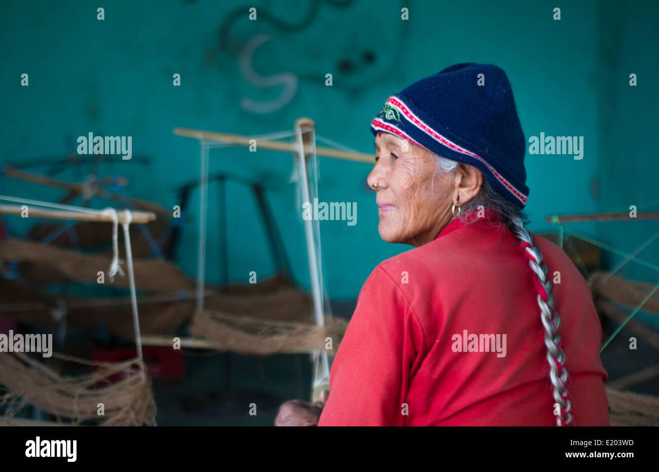 Nepal. Nepali weaving woman, posing and weaving threads for carpets. Nayapati, Eastern Kathmandu. 43 - Stock Image