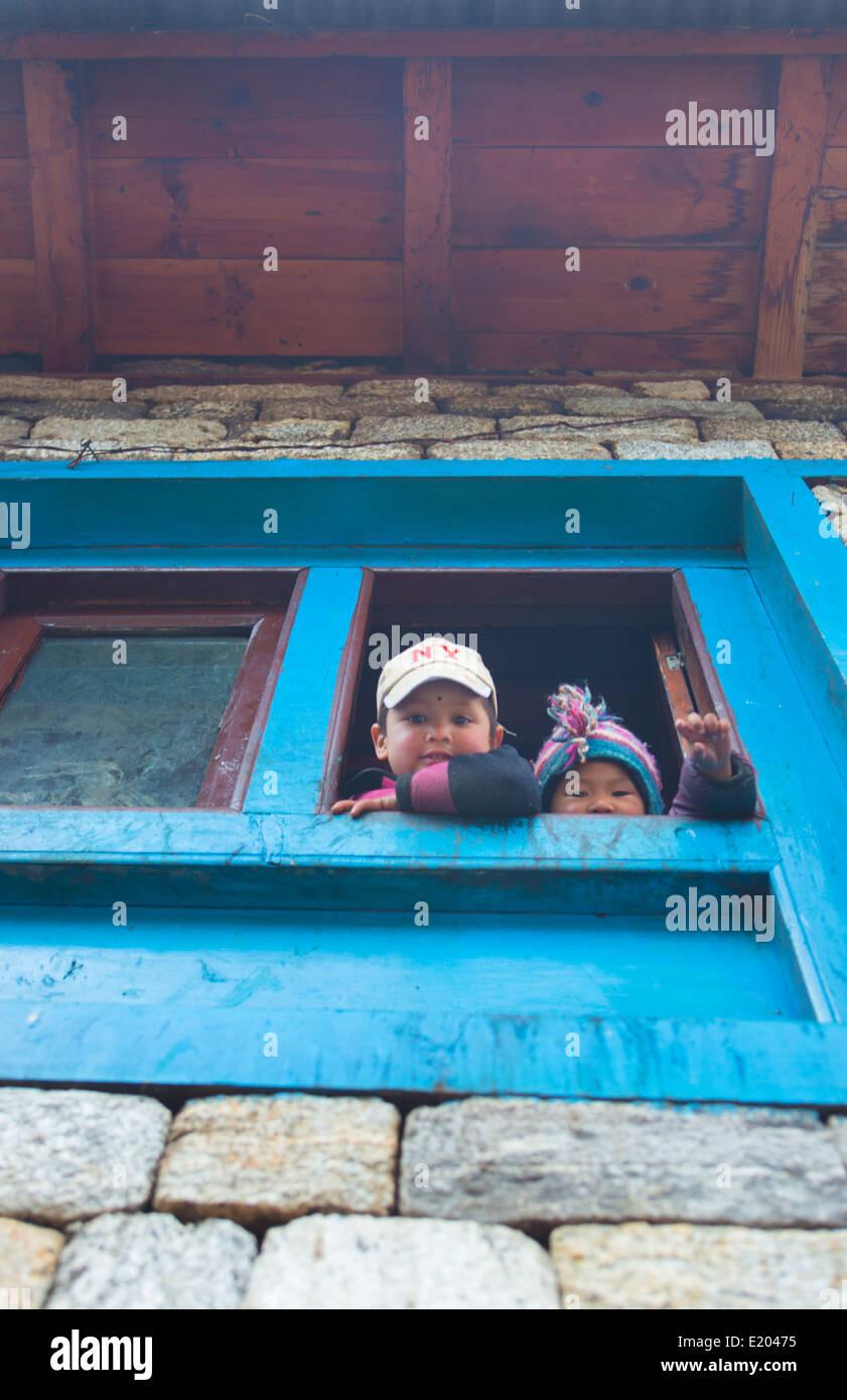 Nepal Himalayas Children peer out window in Phak Ding Solukhumbu remote Mt Everest 56 - Stock Image