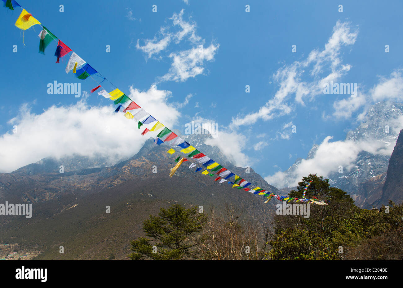Nepal Prayer flags fluttering in the wind with the Himalayas behind them Solukhumbu. - Stock Image