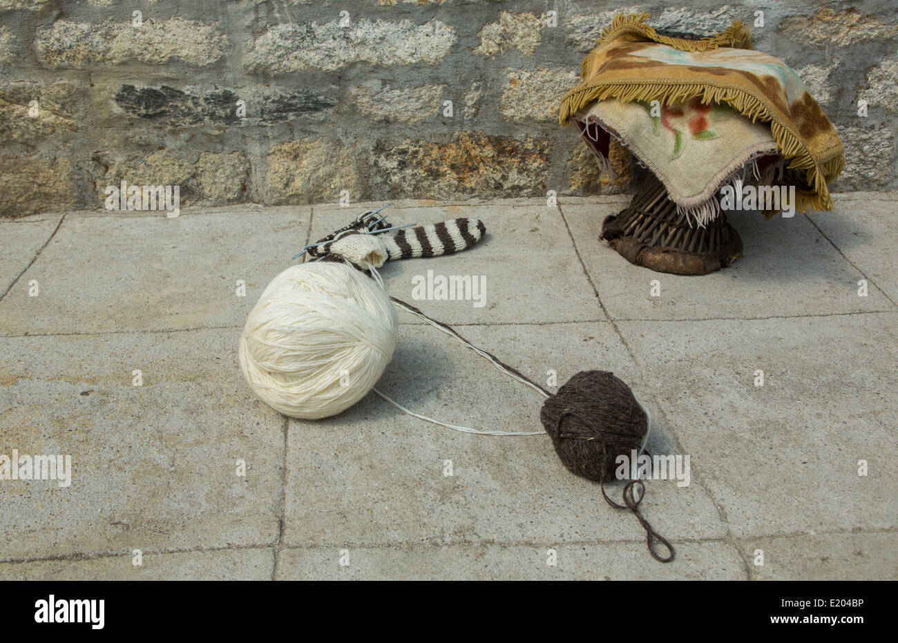 Nepal Yak Wool yarn and a traditional stool sitting against the wall of a Sherpa Tea House in the village of Thamo, - Stock Image