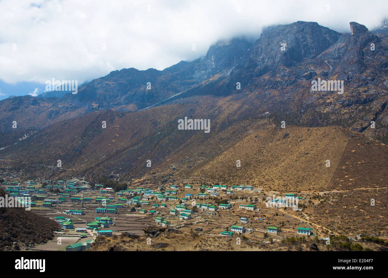 Nepal The village of Khumjung with the cloud-topped Himalayas rising steeply above it. remote, Mt Everest, Himalayas - Stock Image