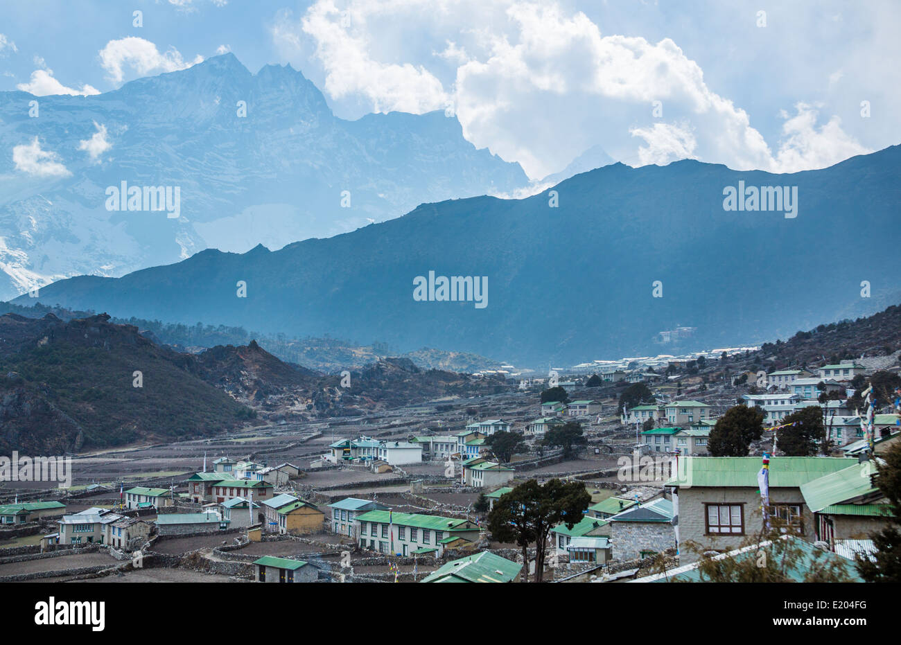 Nepal village of Khumjung in the evening, cast in the shadow of the Himalayas rising in the distance remote, Mt - Stock Image