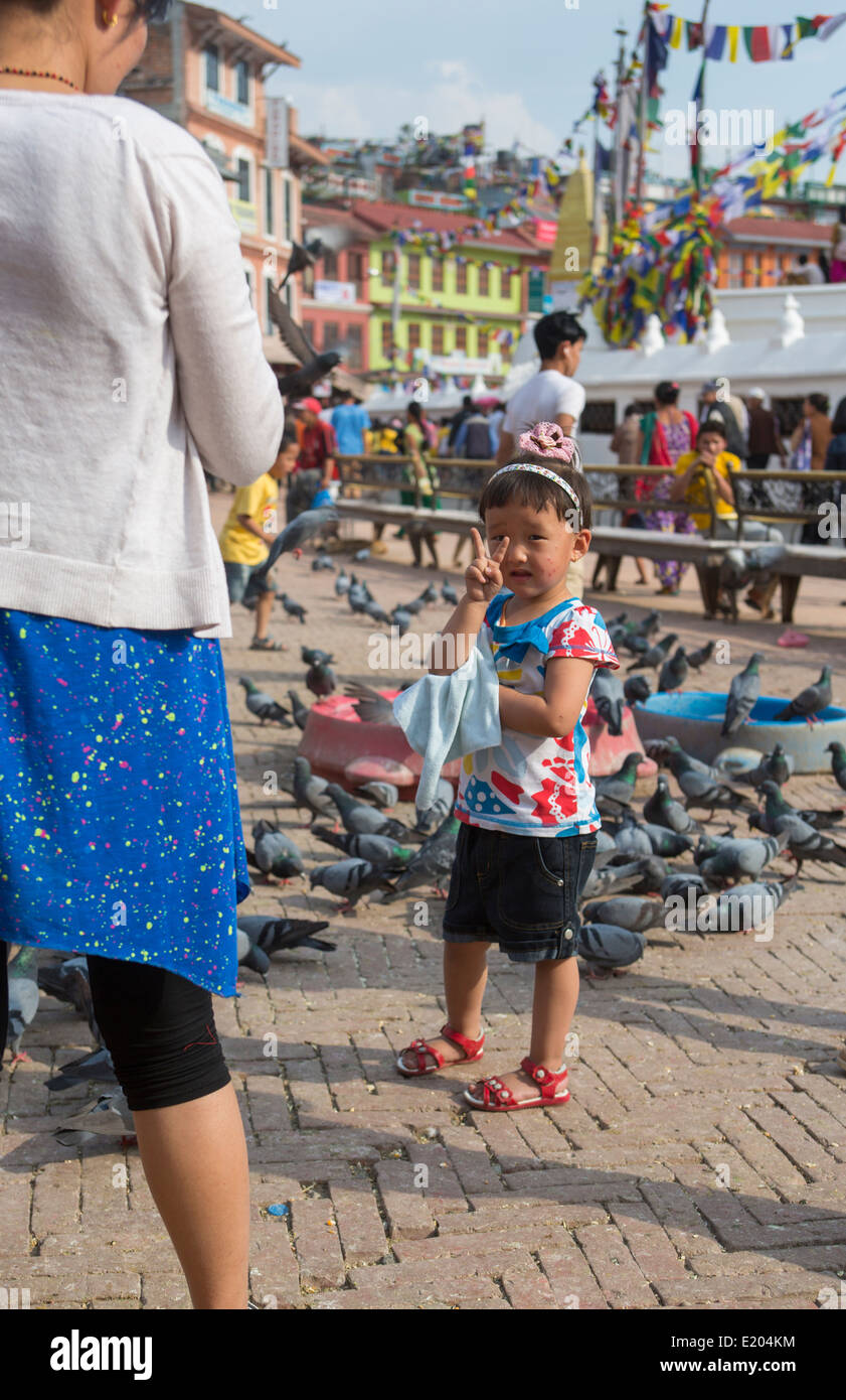 Kathmandu Nepal Girl gives peace sign in front of birds at the Boudhanath Stupa, Kathmandu - Stock Image