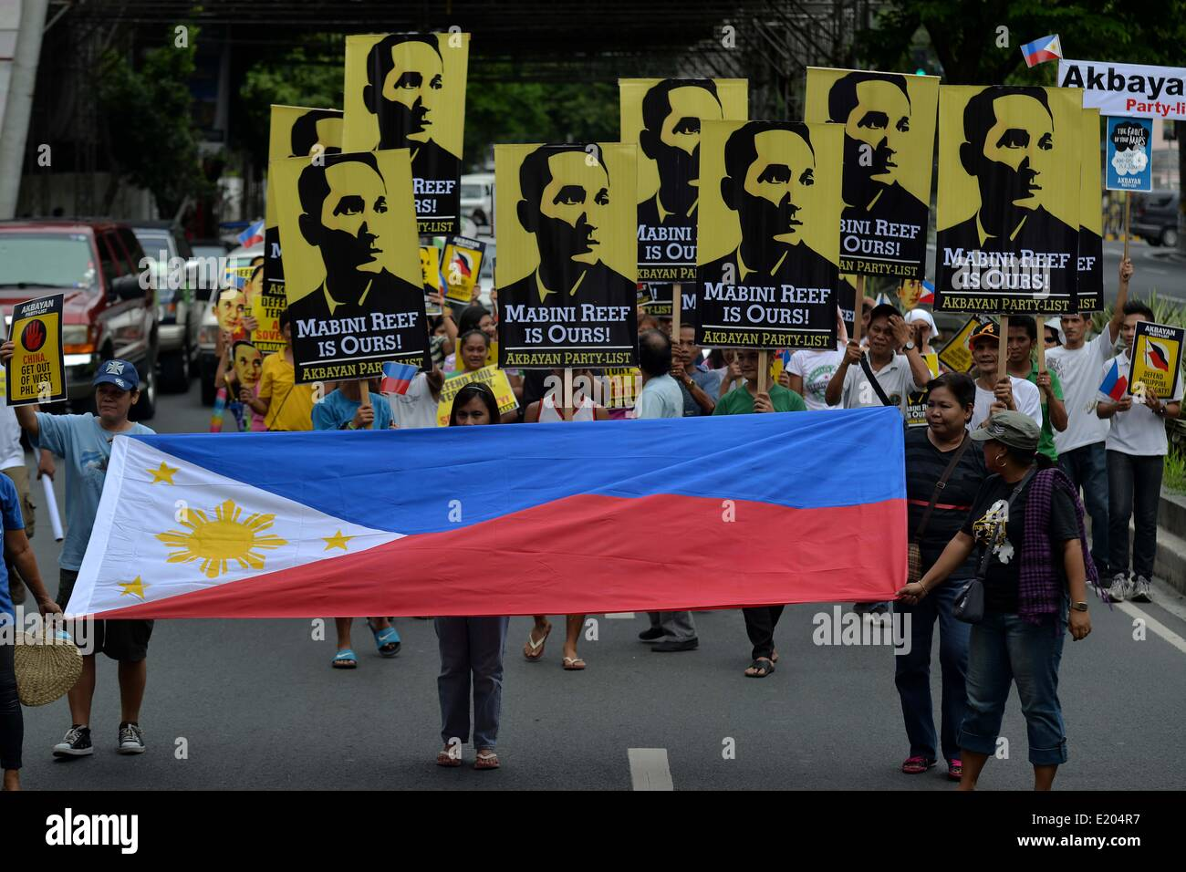 Makati, Philippines. 12th June, 2014. Demonstrators hold placards and the Philippine National flag during a protest - Stock Image