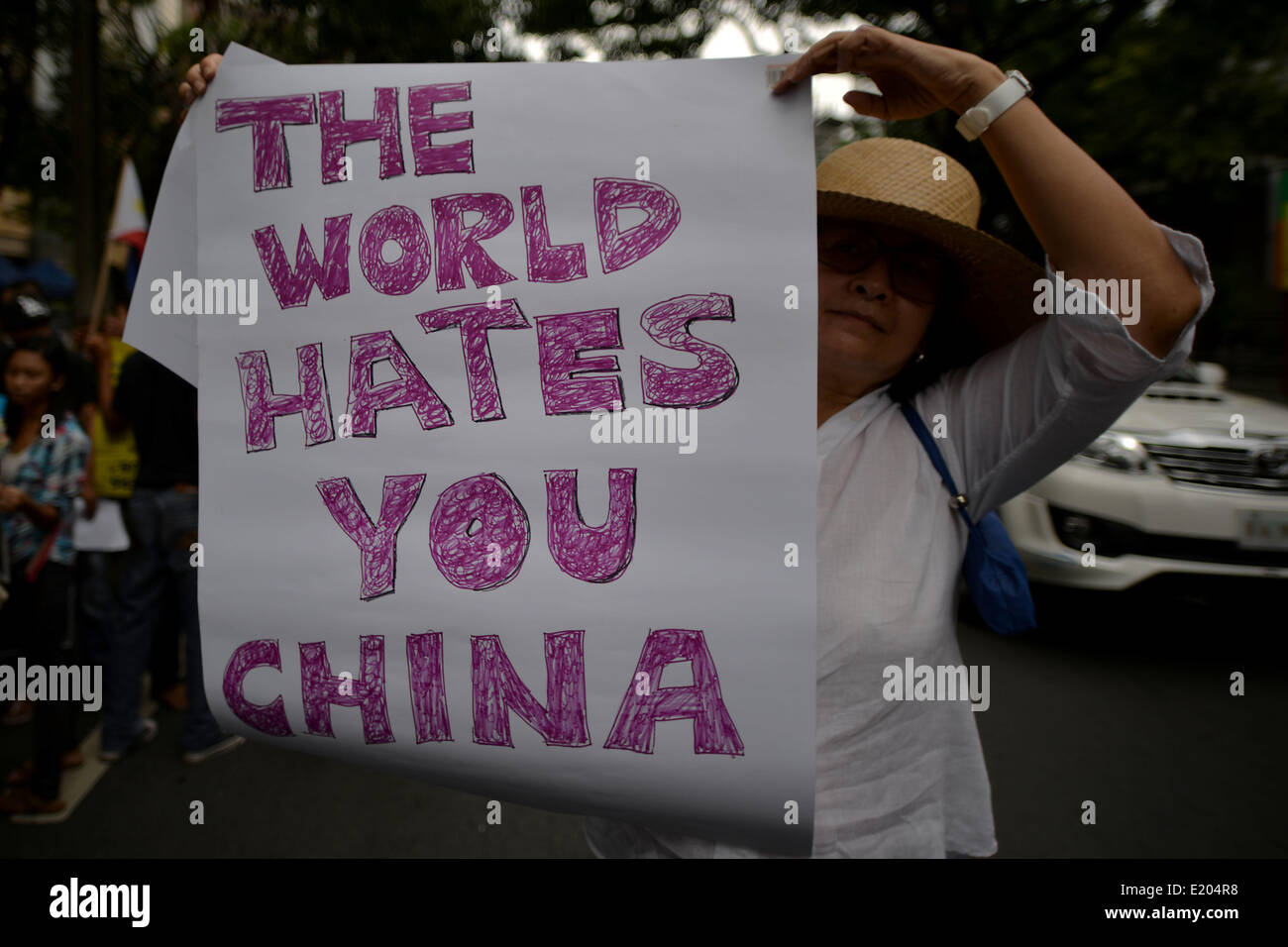 Makati, Philippines. 12th June, 2014. A demonstrator holds a sign during a protest outside the Chinese consulate - Stock Image