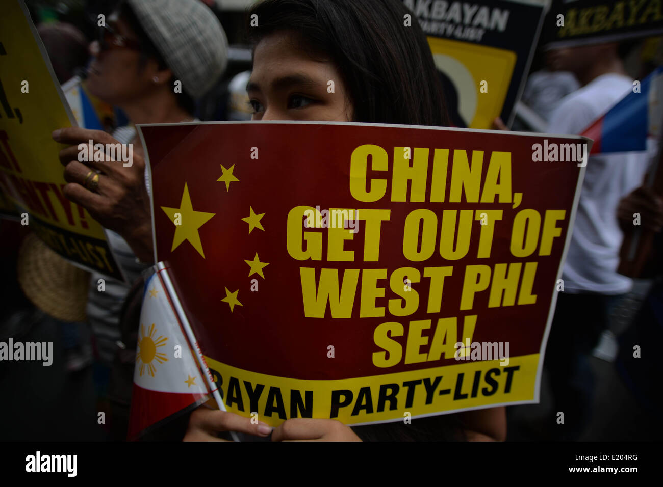 Makati, Philippines. 12th June, 2014. A demonstrator holds a placard during a protest outside the Chinese consulate - Stock Image