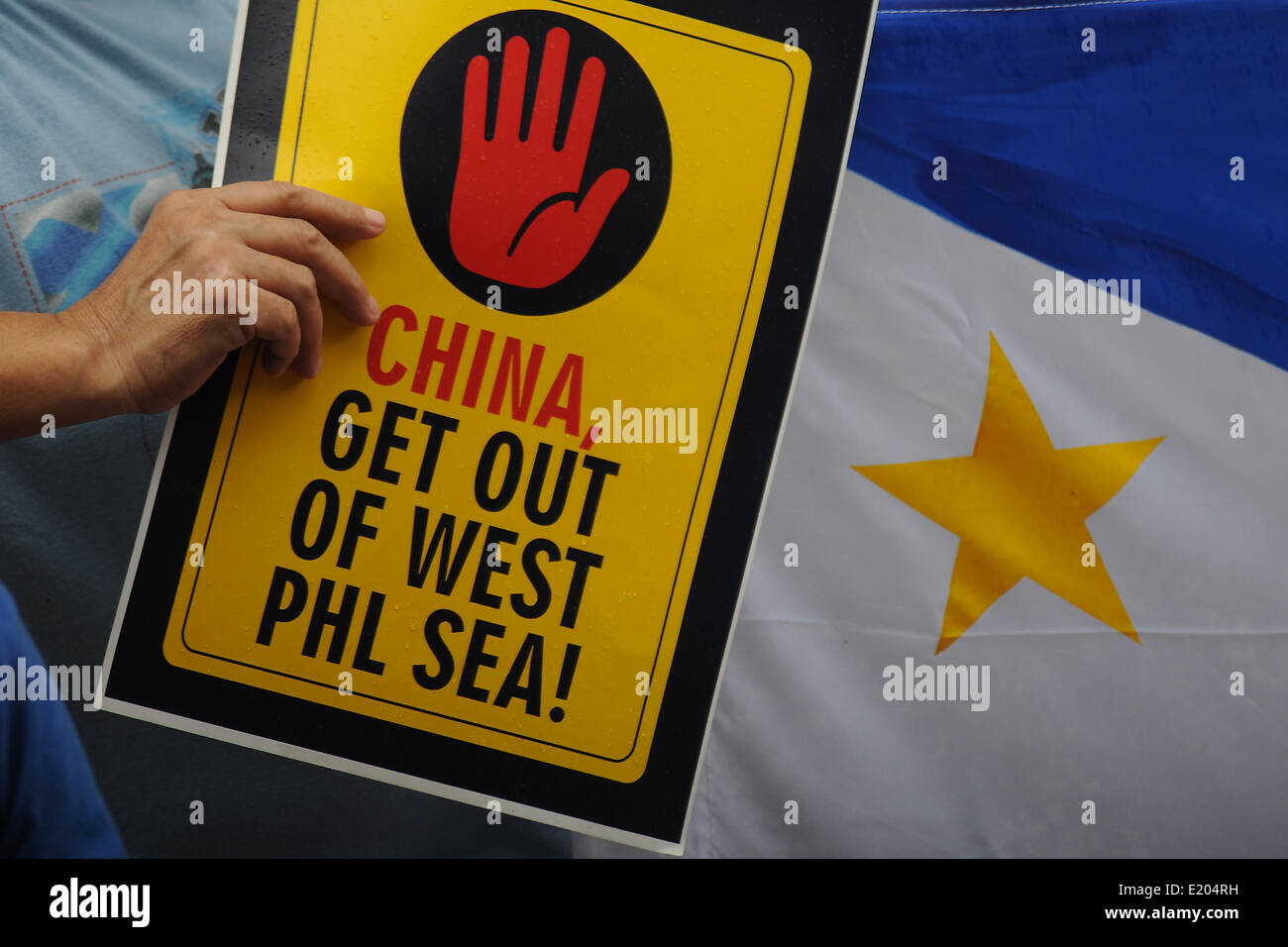 Makati, Philippines. 12th June, 2014. A demonstrator holds a placard next to a Philippine flag during a protest - Stock Image
