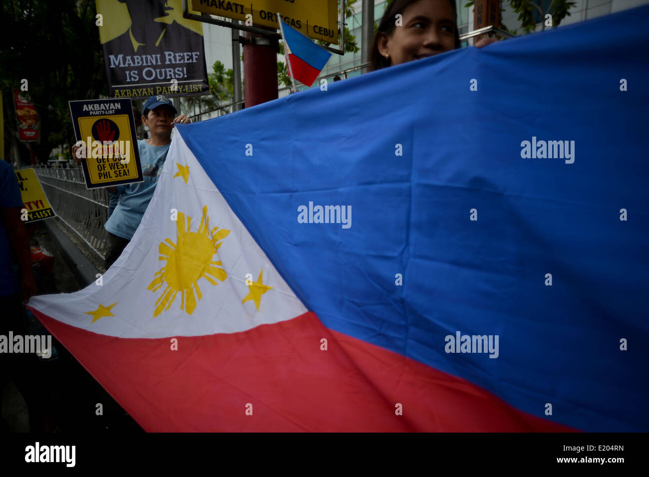 Makati, Philippines. 12th June, 2014. Demonstrators hold up the Philippine national flag during a protest outside - Stock Image