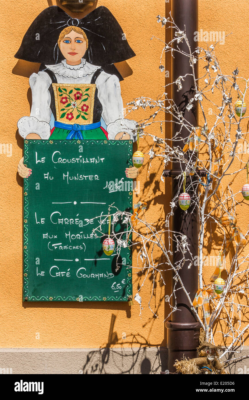 sign of a restaurant showing a young woman in traditional alsatian garb and advertising alsatian culinary specialities Stock Photo