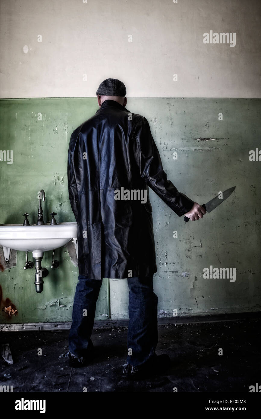 a man in dark clothes with a knife in an abandoned house - Stock Image