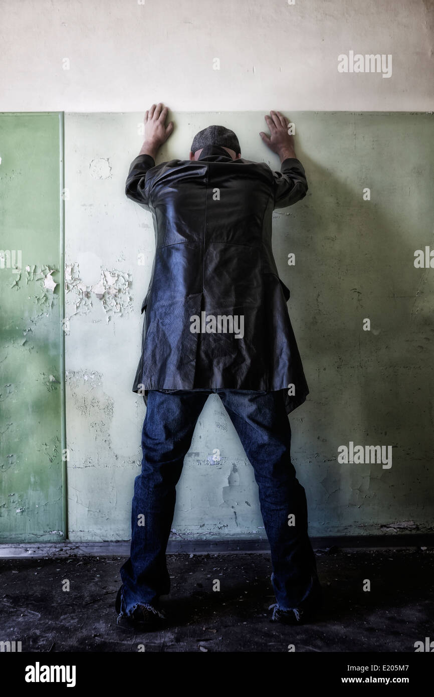 a man in dark clothes is leaning against a wall in an abandoned house - Stock Image
