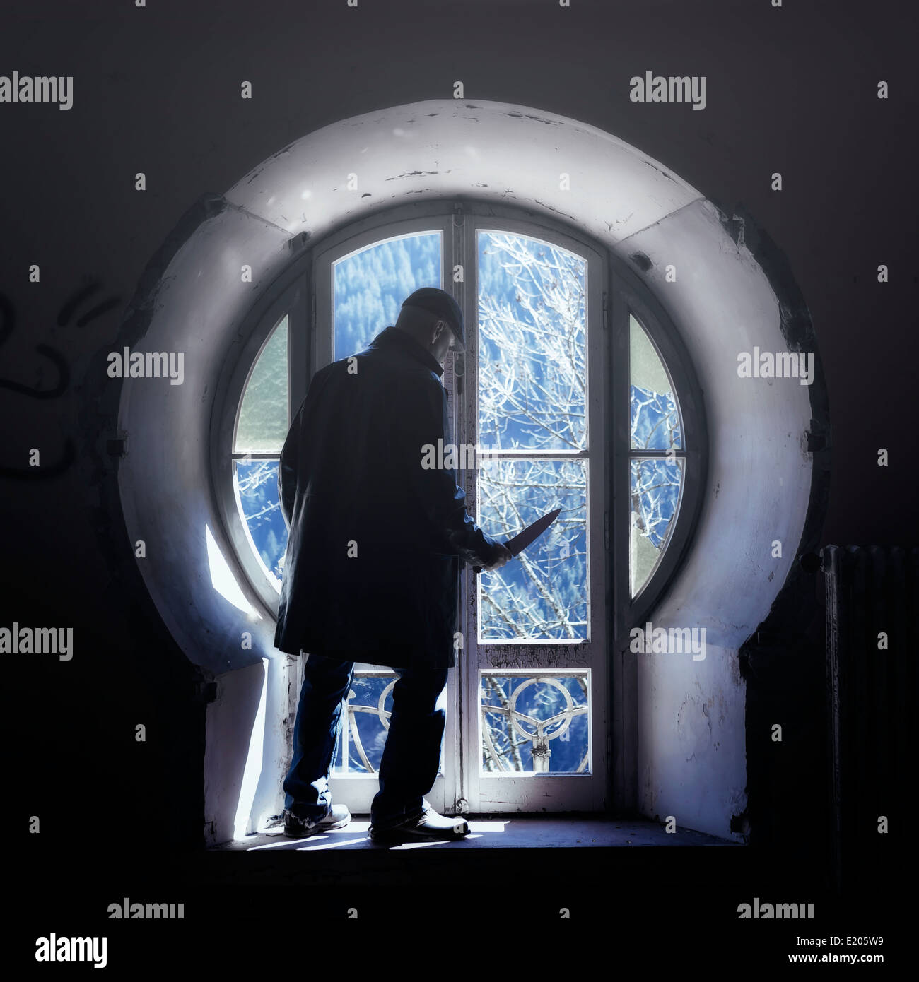 a man with a knife in front of an old window in an abandoned building - Stock Image
