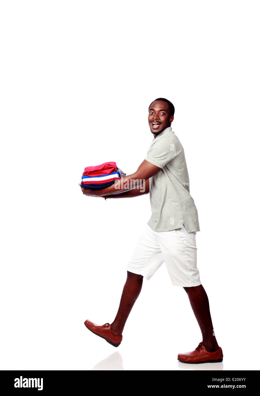 Studio shot of a happy african man holding his clothes over white background - Stock Image