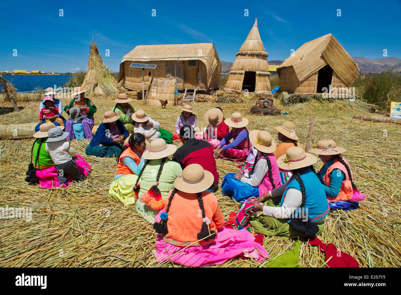Women of the Uro Indians sit in front of typical reed huts, floating islands made of totora reeds, Lake Titicaca, - Stock Image