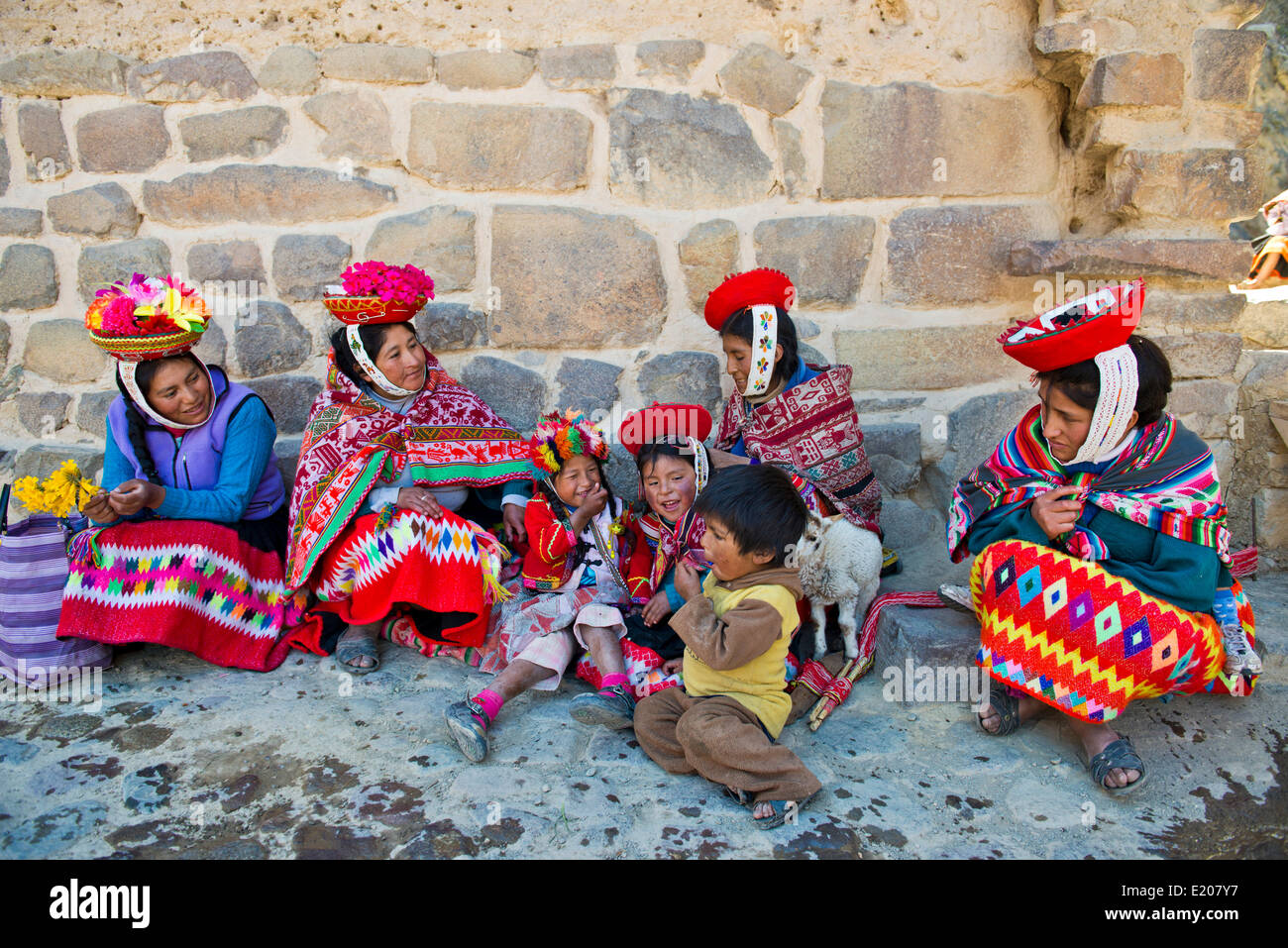 Women and children in traditional dress of the Quechua Indians sitting on the floor in front of a wall, Ollantaytambo - Stock Image