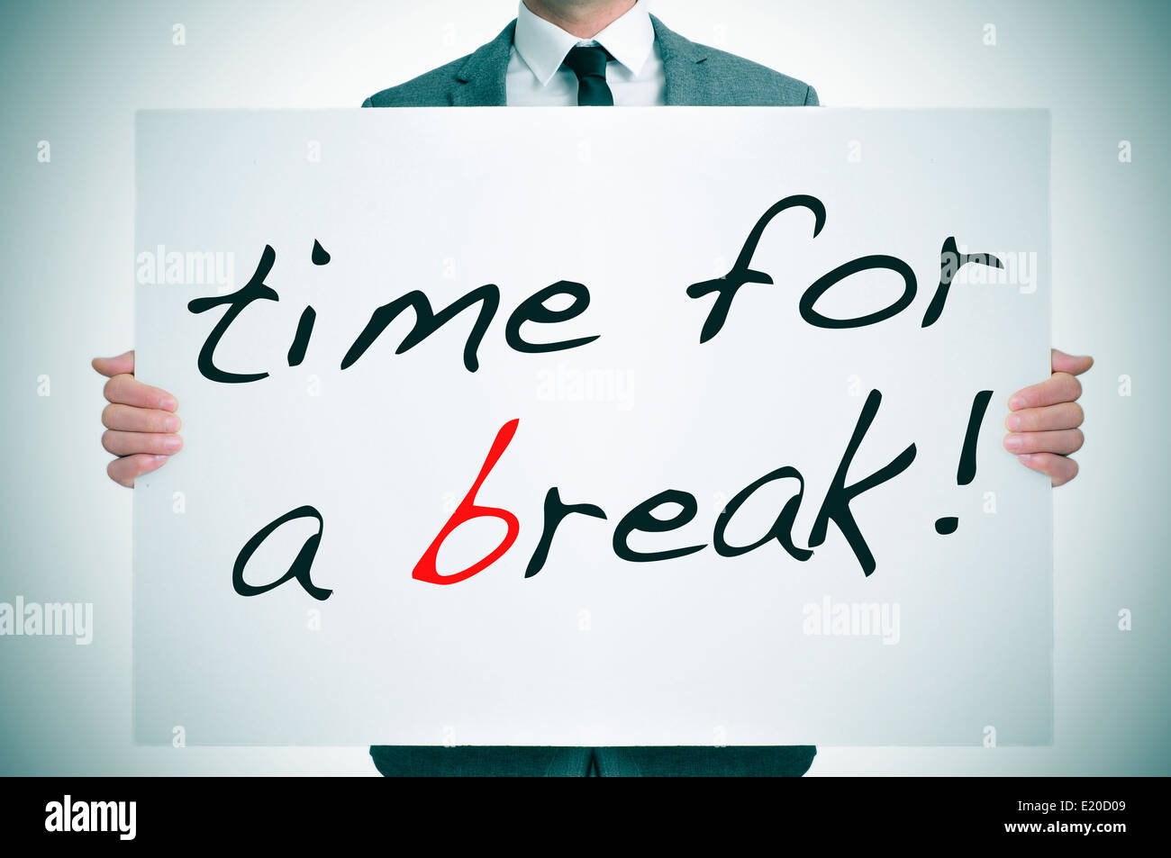 businessman holding a signboard with the text time for a break written in it - Stock Image