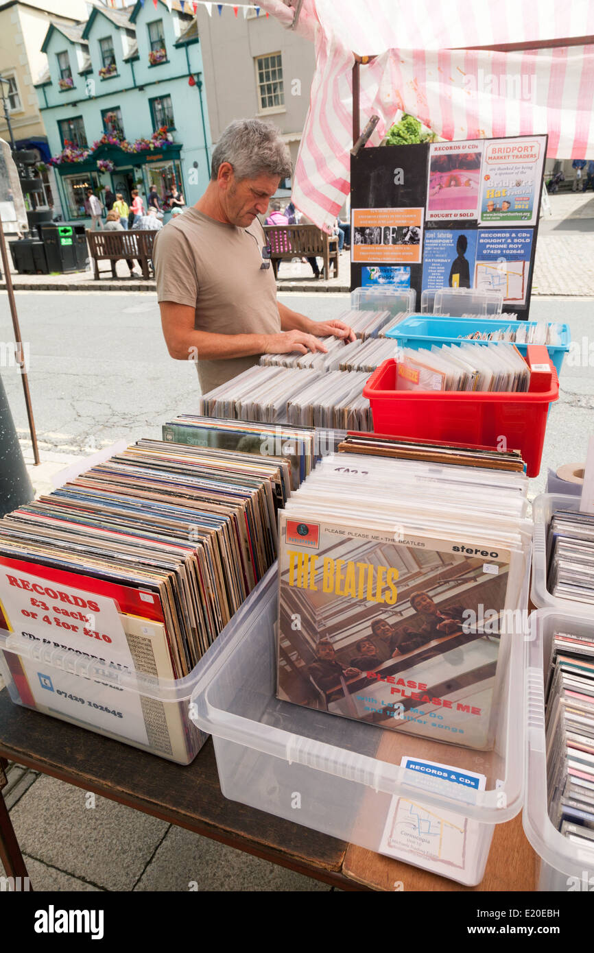 A man shopping for second hand or used Vinyl records in a village market stall, Bridport Dorset England, UK - Stock Image