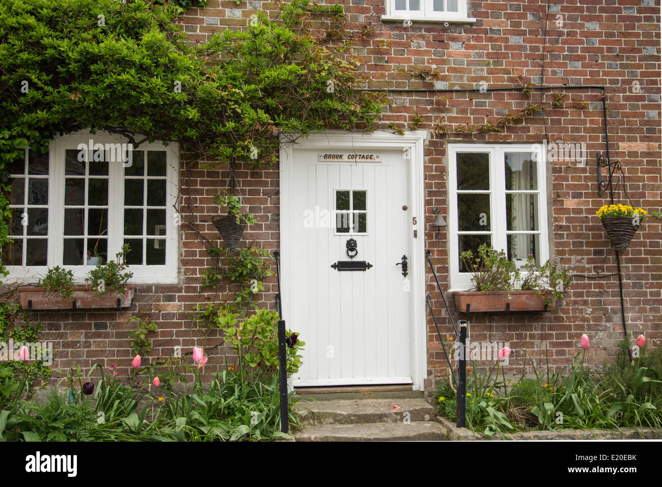 Close Up Of Traditional Cottage With White Front Door In The Stock