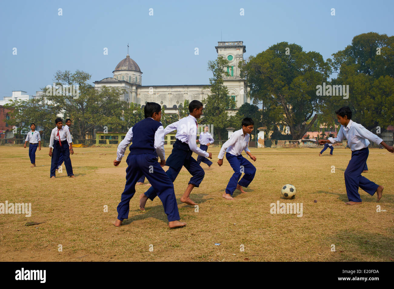 India, West Bengal, Chandernagor (Chandannagar), former French colony, Sacred Heart church, student playing football - Stock Image