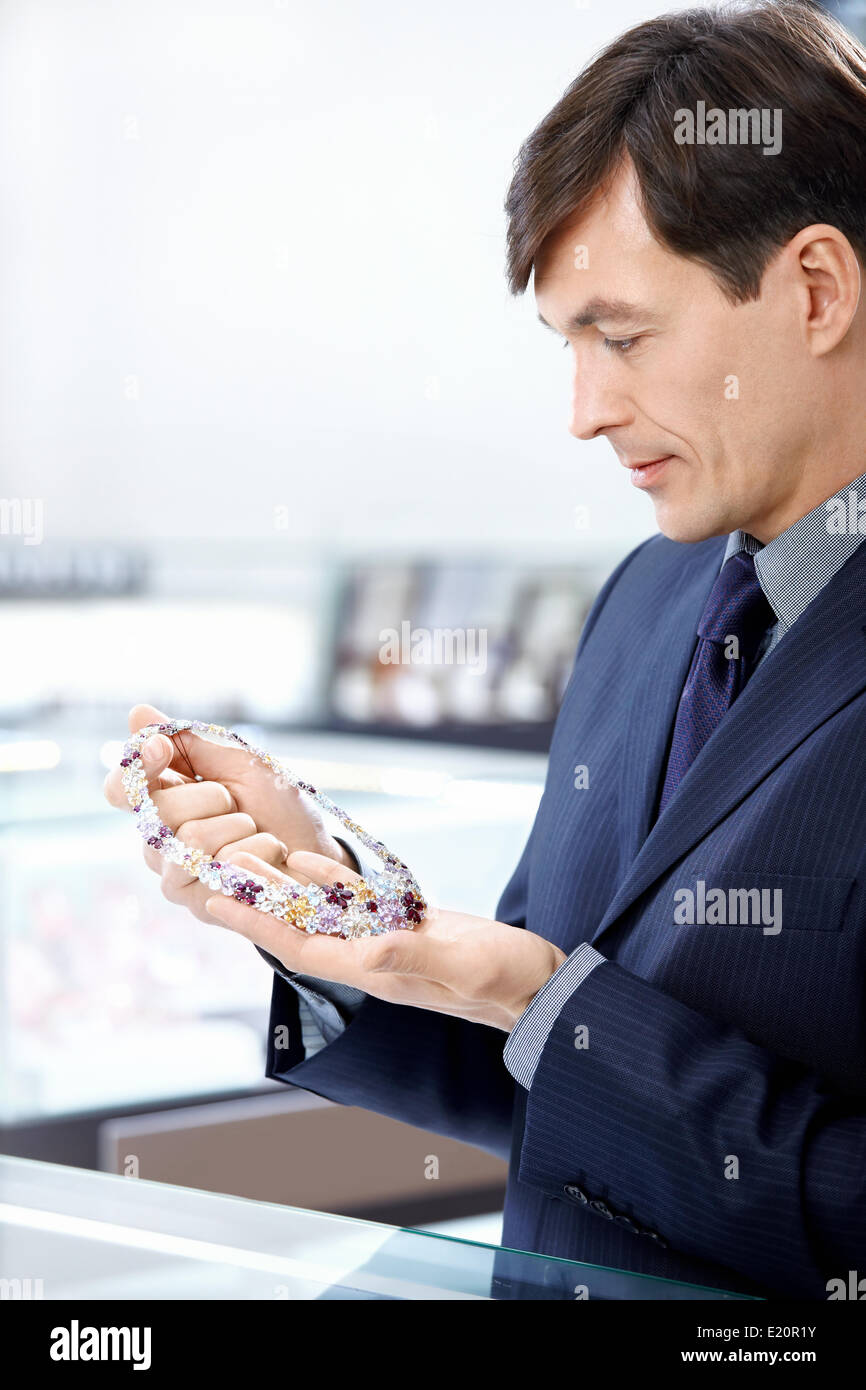 The man aged considers a jeweller necklace - Stock Image
