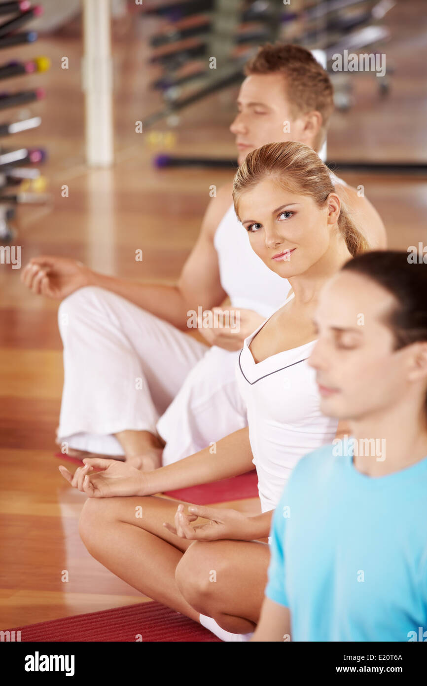 Three persons sit in a lotus pose - Stock Image