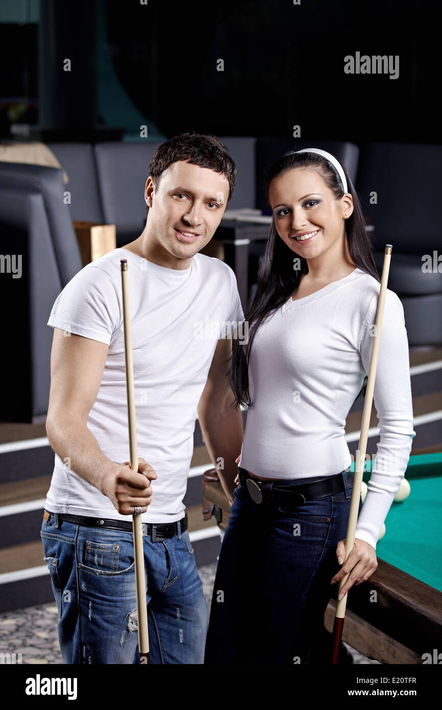 Young couple with cue at a billiard table - Stock Image