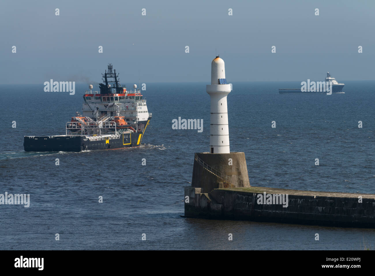 An oil supply vessel leaves Aberdeen harbour for the North Sea with the breakwater and light house in the foreground. - Stock Image
