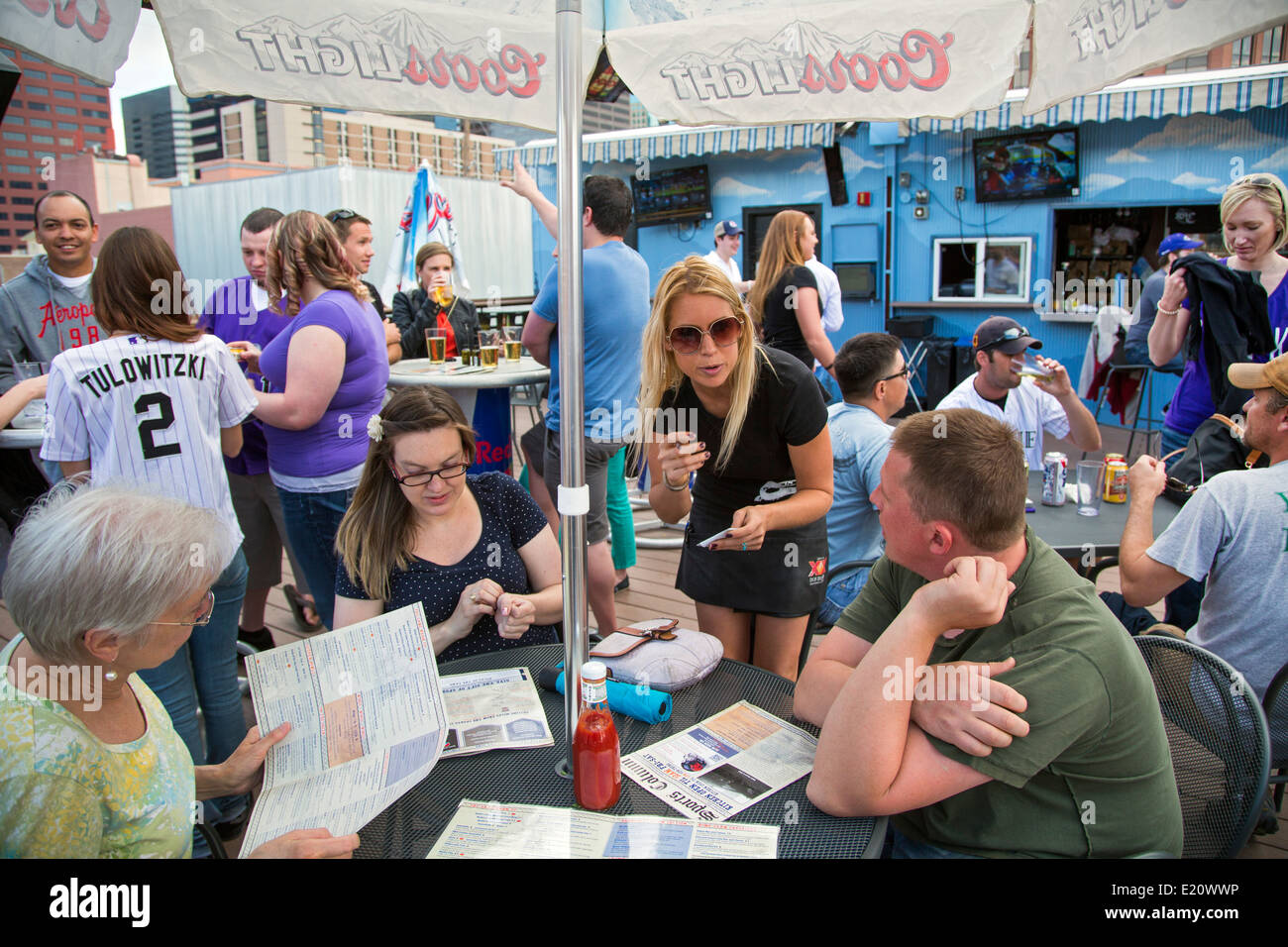 Denver, Colorado - A server takes orders from baseball fans on the outdoor deck of the Sports Column. - Stock Image