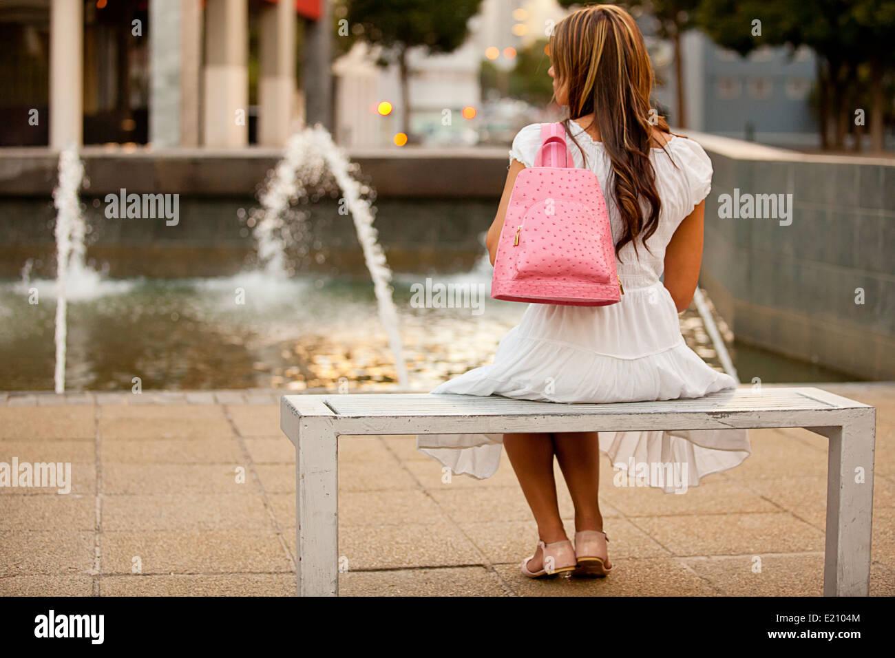 Feminine lady modeling a pink leather backpack wearing blue denim shirt and white skirt - Stock Image
