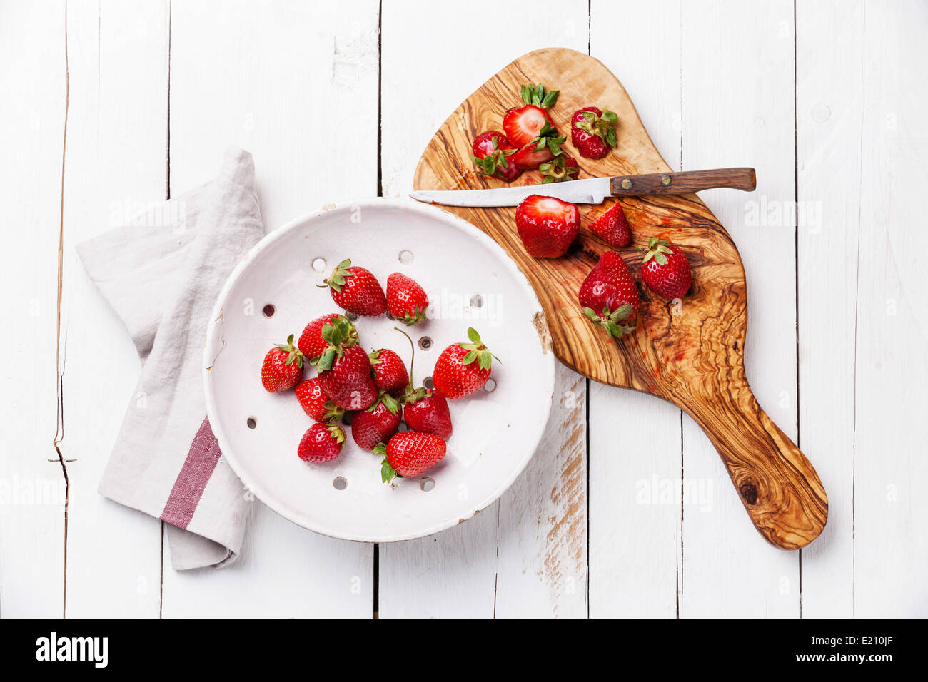 Strawberry in Vintage ceramic colander on white wooden background - Stock Image