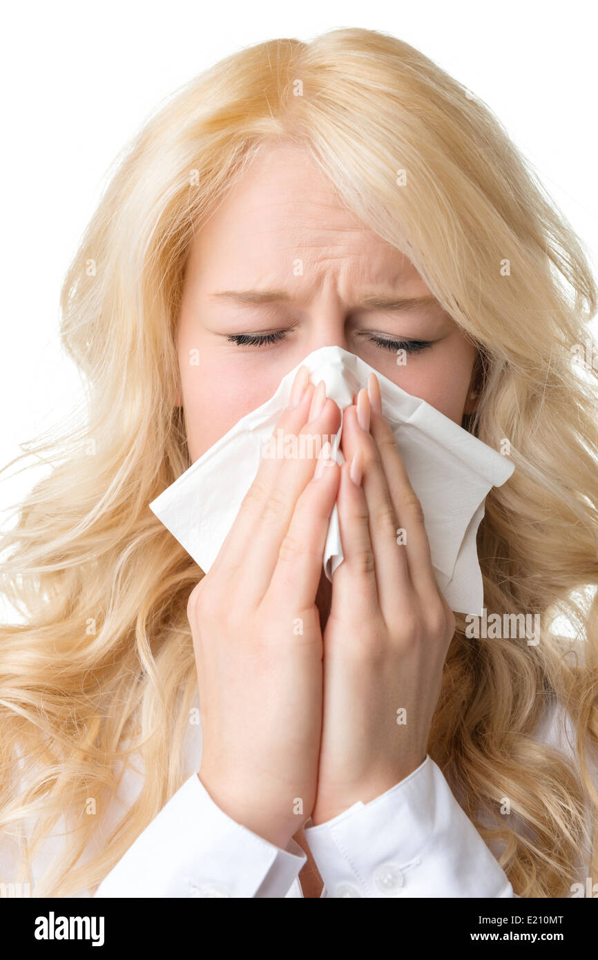 Portrait of a ill blond woman who is sneezing in a tissue - Stock Image