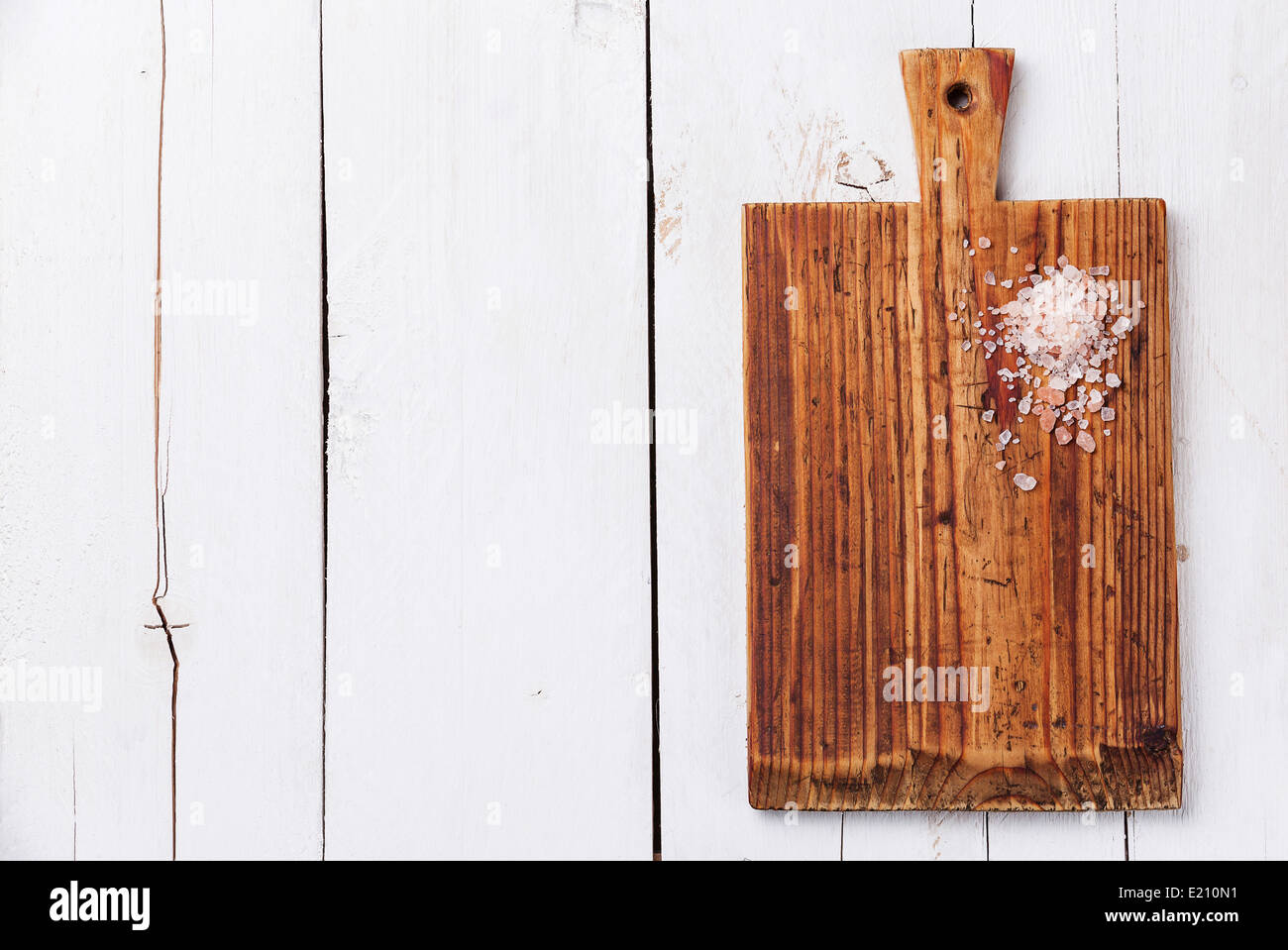 Pink salt on Kitchen Cutting board on white wooden texture background - Stock Image