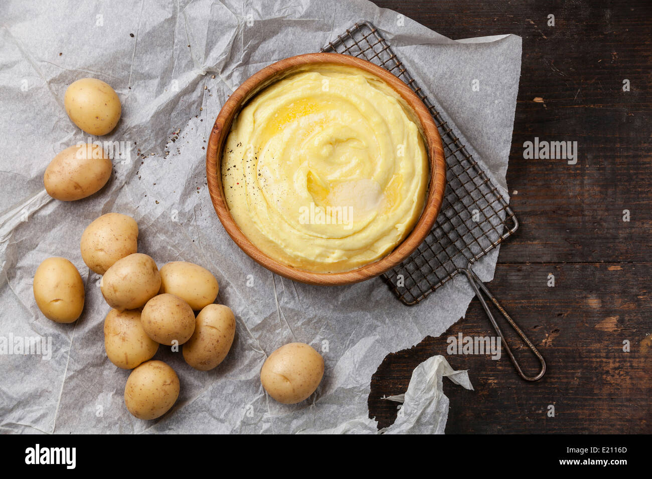 Mashed potatoes and raw potatoes on dark wooden background - Stock Image