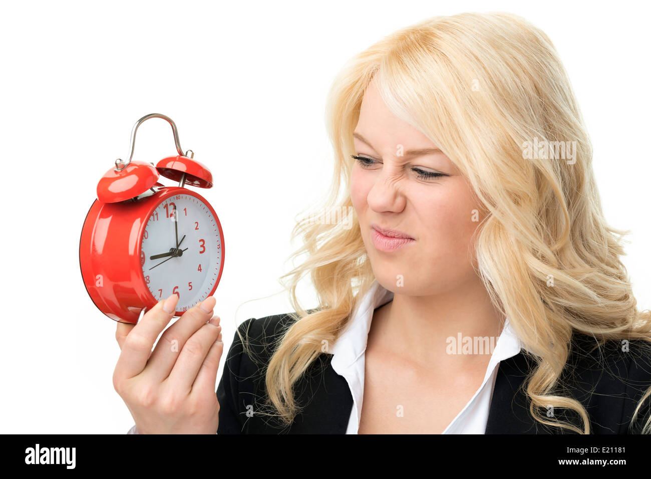 Laughing blond woman unhappy with red alarm clock - Stock Image