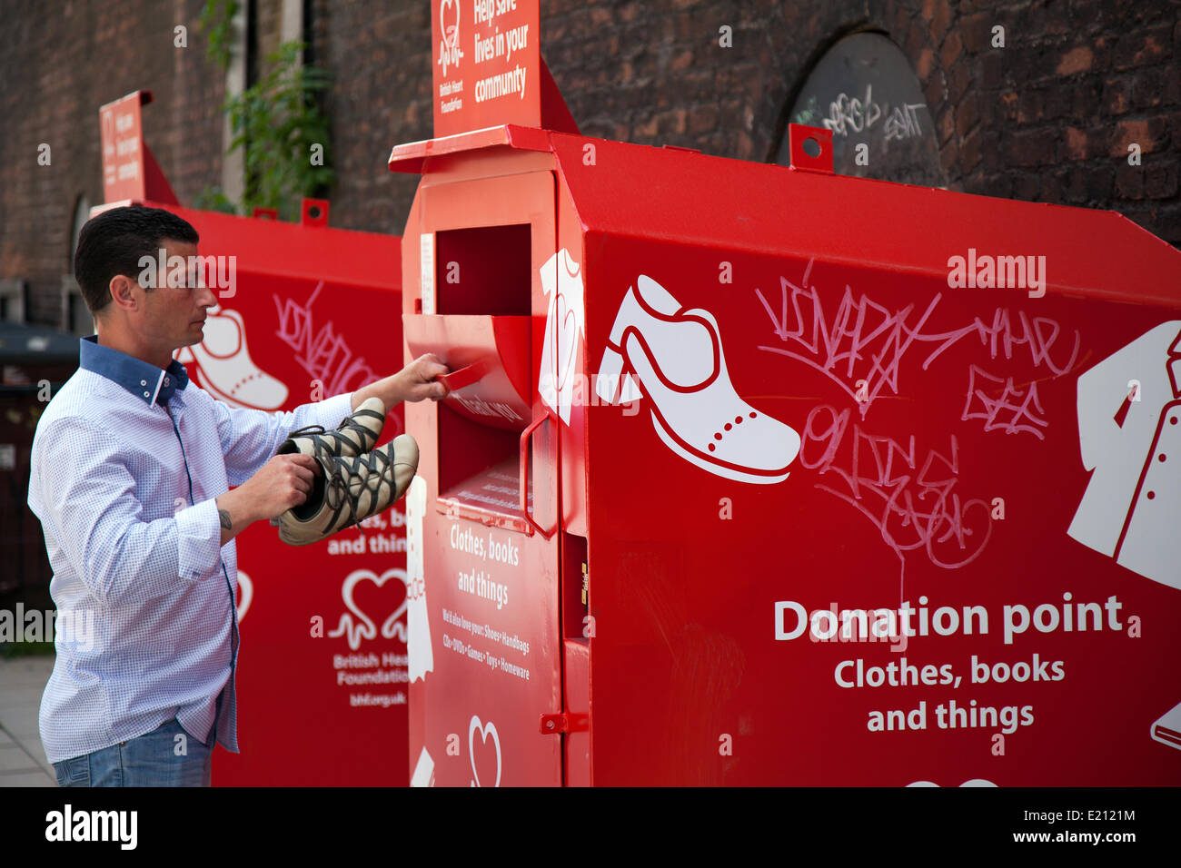 Man (MR) at donation point, clothing charity clothes donate giving charitable used container give secondhand poor - Stock Image