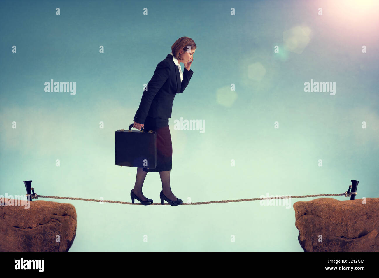 confident businesswoman walking a tightrope or highwire multitasking - Stock Image