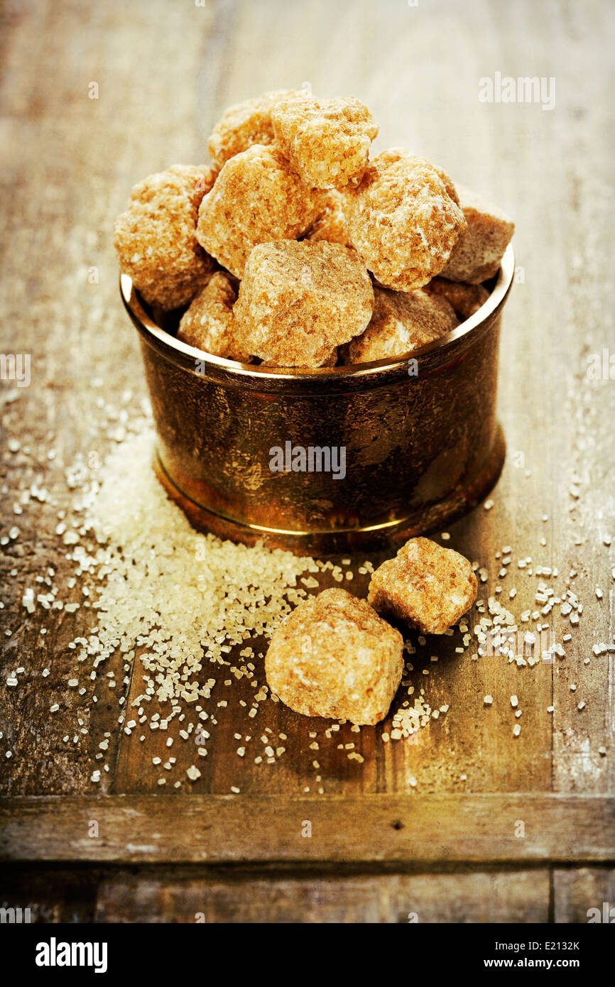 Close-up of brown sugar on old wooden table - Stock Image