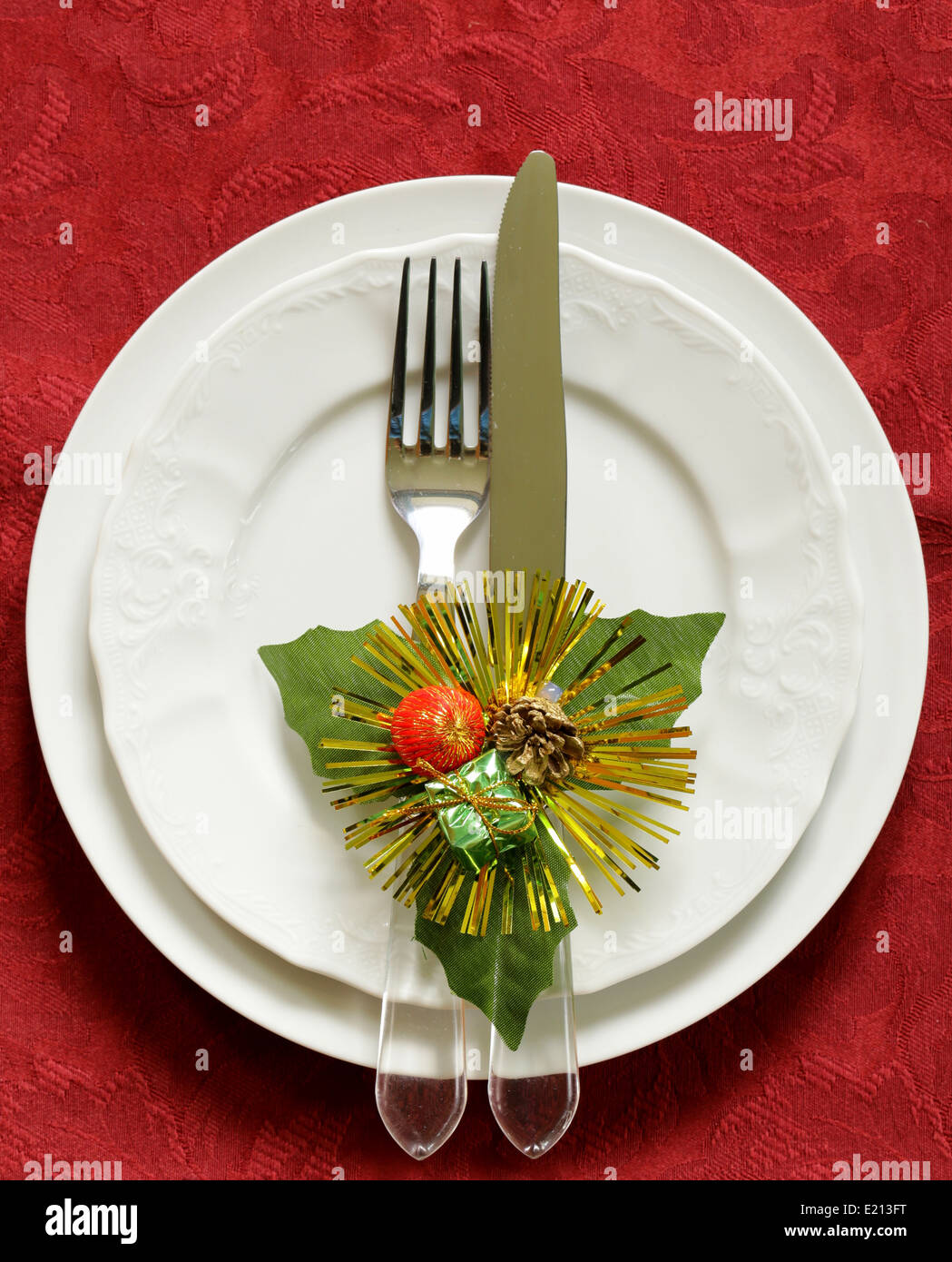 Christmas table setting (white plates on a red background) - Stock Image