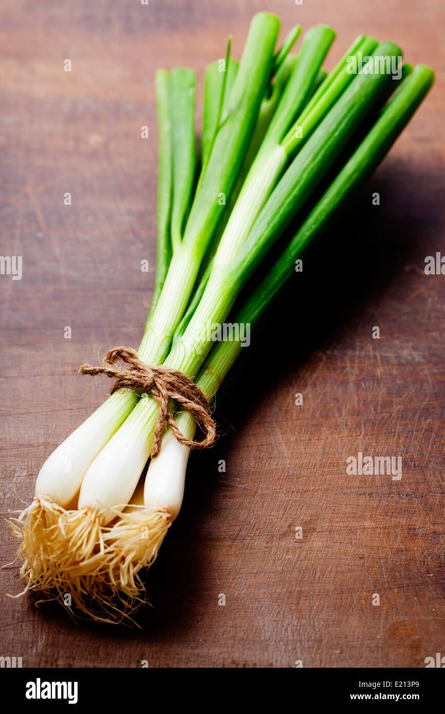 fresh spring onions on a wooden board - Stock Image