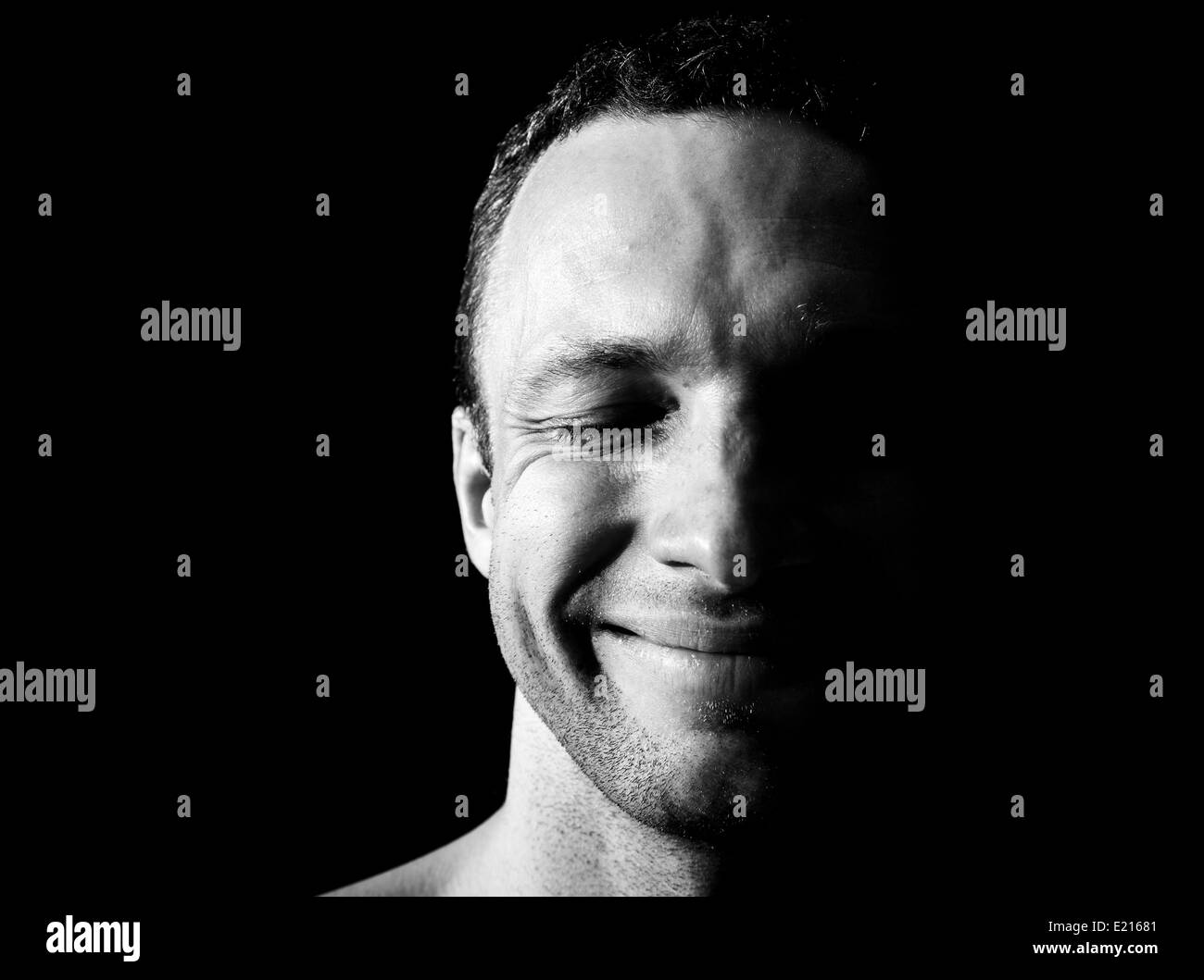 Young smiling Caucasian man portrait on black background - Stock Image