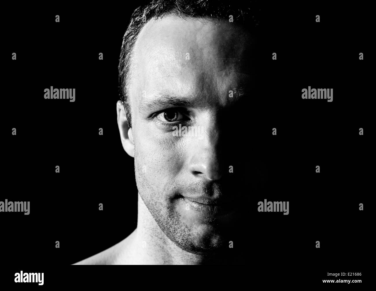 Young smiling Caucasian man closeup portrait on black background - Stock Image